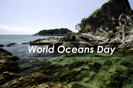the oceans: image concept with word WORLD OCEANS DAY.blurred background beautiful nature sea view from the rocky shore. clear water surrounded the island at sunny day.