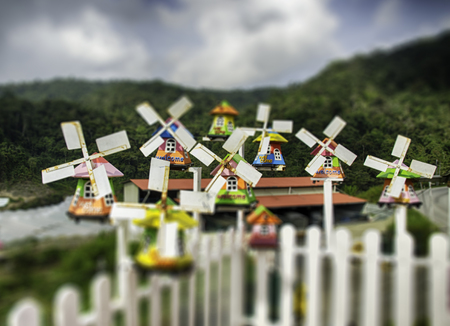 tilt views: group of miniature traditional Dutch old wooden windmill with top hill view, cloudy sky and hill background