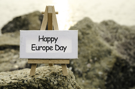 observance: Image concept with word HAPPY EUROPE DAY on white canvas and easel. blurred rock image background at the shore during sunset.