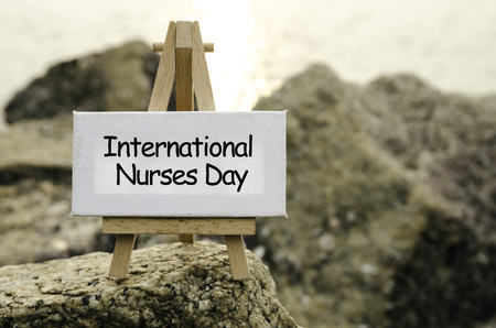 maternal: Image concept with word INTERNATIONAL NURSES DAY on white canvas and easel. blurred rock image background at the shore during sunset. Stock Photo