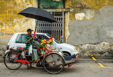building wall: PENANG, MALAYSIA-30 DECEMBER 2011: unidentified man standing beside his trishaw. iconic traditional transportation in Penang, Malaysia.