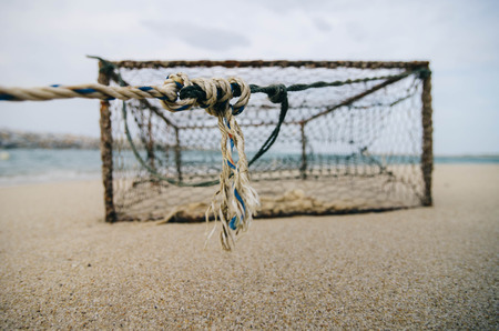 crab pot: closeup and selective focus on rope over rusty crab pot on the sandy beach. Stock Photo
