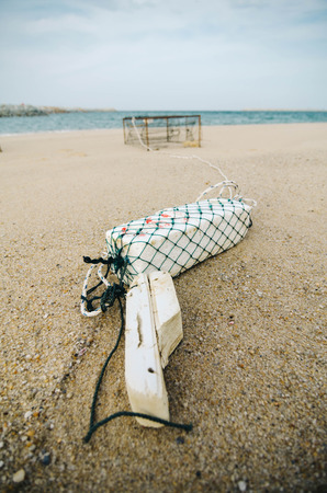 crab pot: white fish buoy on sandy beach over crab pot background.focus on white buoy.shallow depth of field