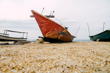 red fisherman fiber boat on the sandy beach with white cloudy sky.surface level shot and selective focus on red boat