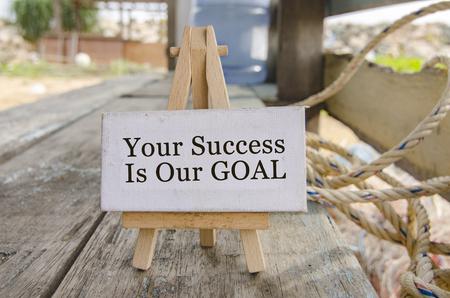 customer services concept met woord uw succes is ons doel. wahite canvas op schildersezel over onscherpe achtergrond