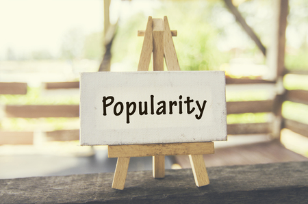 popularity: Business marketing concept, word POPULARITY on white canvas and wooden easel over blurred background at sunny day.
