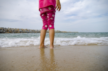 cropped out: cropped and out of focus image. little girls standing standing on a sandy beach and play with waves at sunny day Stock Photo