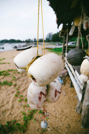 blurred and selective focus image of hanging white dirty fish net buoy tied together with yellow rope under wooden fottage.