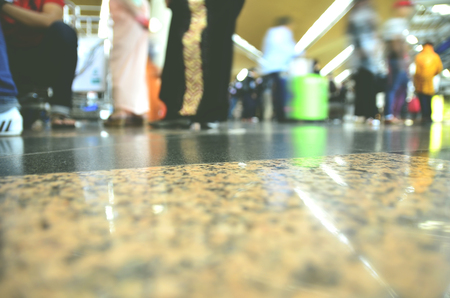 floor level: blurred image and surface level shot people standing in airport.reflection on the floor and blur motion people movement