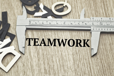 vernier caliper: Business motivation and finance concept, vernier caliper with word TEAMWORK over wooden floor and alphabetical word made from wood background