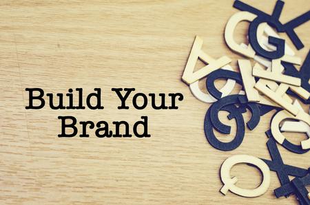 image conceptuelle, mot construire votre marque sur fond en bois. mot de l'alphabet à droite