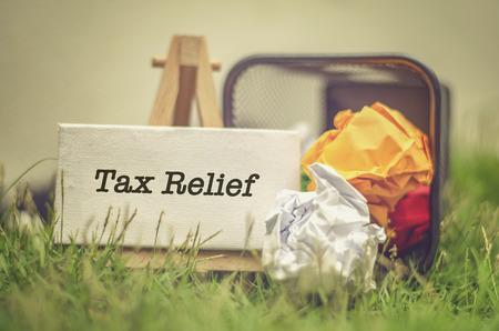 Contabilidad financiera Concepto impuestos. palabra Alivio de Impuestos sobre lienzo en blanco y caballete. tono de color retro y disparo de enfoque selectivo