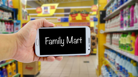 mart: image concept, cropped hand holding smartphone with word FAMILY MART over blurred hypermarket background