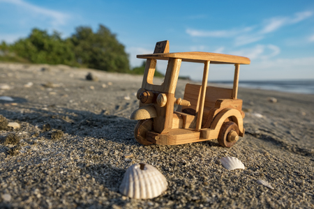 travel image concept, wooden miniature tuk-tuk, most iconic Thailand transportation over beach background