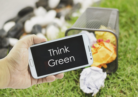 concept image, hand holding mobile phone with word THINK GREEN over blurred background.crumple color paper in bin,green grass and stone