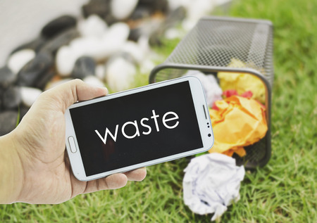 concept image, hand holding mobile phone with word WASTE over blurred background.crumple color paper in bin,green grass and stone