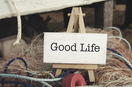 nylon: image concept, word Good Life on white canvas frame and wooden easel over blurred background. wooden cottage and nylon fishing net with round buoy