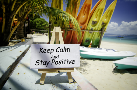 conceptual image with word KEEP CALM AND STAY POSITIVE on white canvas frame and wooden easel. Blurred image of beach and colorful kayaks background at sunny day.