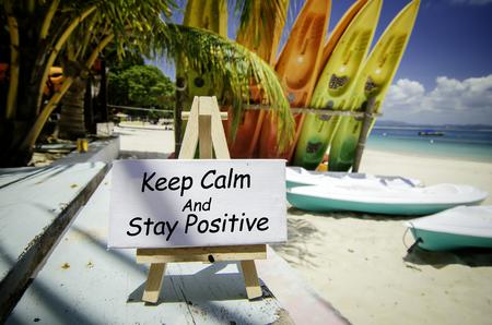 conceptueel beeld met woord HOUD KALM EN BLIJF POSITIEF op wit canvasframe en houten schildersezel. Wazig beeld van strand en kleurrijke kajaksachtergrond bij zonnige dag.