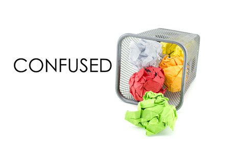 paperless: conceptual image of green, red and yellow waste color paper with word CONFUSED. isolated white background