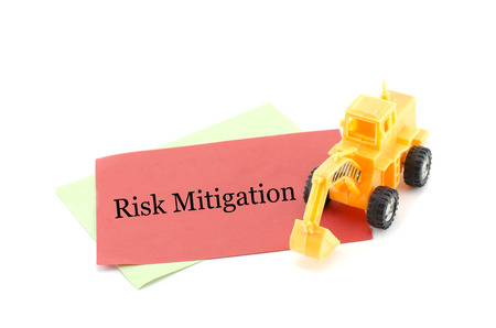 mitigation: image concept yellow toy bulldozer on red paper with word RISK MITIGATION. isolated white background