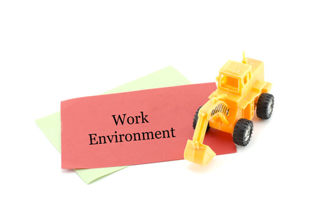 work environment: image concept yellow toy bulldozer on red paper with word WORK ENVIRONMENT. isolated white background Stock Photo