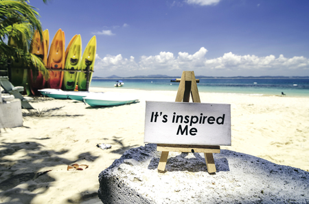 conceptual image,white canvas frame and wooden easel with word IT INSPIRED ME. Tropical beach  at sunny day ,white sand,colorful kayaks and clear blue water background. Stock Photo
