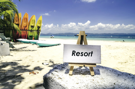 conceptual image,white canvas frame and wooden easel with word RESORT. Tropical beach  at sunny day ,white sand,colorful kayaks and clear blue water background. Stock Photo