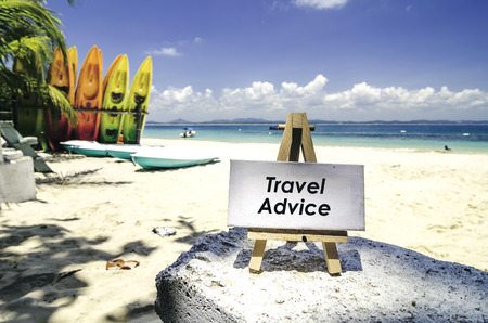 white canvas frame and wooden easel with word TRAVEL ADVICE. Tropical beach  at sunny day ,white sand,colorful kayaks and clear blue water background.