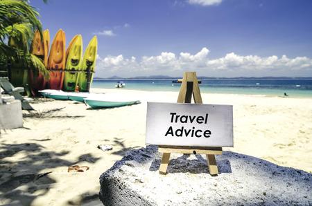 wit canvas frame en houten ezel met word TRAVEL ADVIES. Tropisch strand bij zonnige dag, wit zand, kleurrijke kajaks en duidelijke blauwe waterachtergrond.