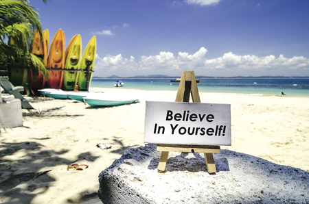 conceptual image,white canvas frame and wooden easel with word BELIEVE IN YOURSELF. Tropical beach  at sunny day ,white sand,colorful kayaks and clear blue water background