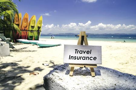wit canvas frame en houten ezel met woord TRAVEL VERZEKERING. Tropisch strand bij zonnige dag, wit zand, kleurrijke kajaks en duidelijke blauwe waterachtergrond.