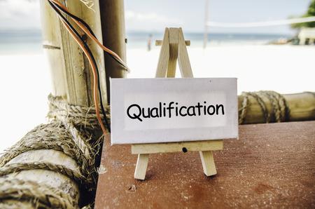 Begriffsbild, Wort QUALIFICATION auf weißem Segeltuch und Gestell Bambushütte mit tropischem Strandhintergrund am sonnigen Tag Standard-Bild
