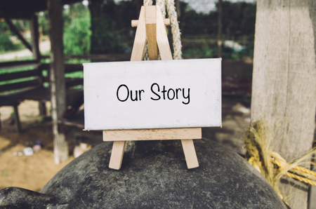 our: image concept, word OUR STORY on white canvas and wooden easel over blurred background