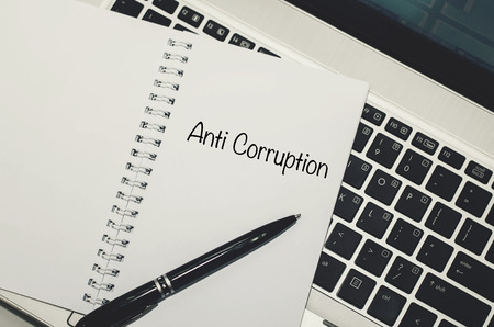 unethical: conceptual image, word ANTI CORRUPTION on white book over laptop background.black ball pen and keyboard.