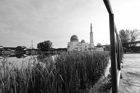 Black and white image of Tranquil lake surrounded As-Salam Mosque located in Selangor, Malaysia with reflection on the lake.