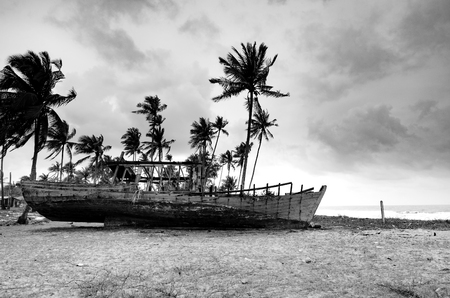 black and white image stranded wooden shipwrecked on the sandy beach over cloudy sky background
