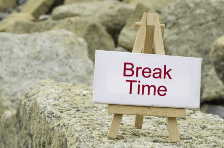 time frame: conceptual image,  word BREAK TIME on white canvas frame and wooden tripod stand.blur rock textures background