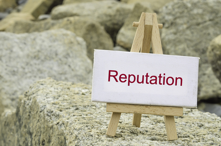 conceptual image,  word REPUTATION on white canvas frame and wooden tripod stand.blur rock textures background
