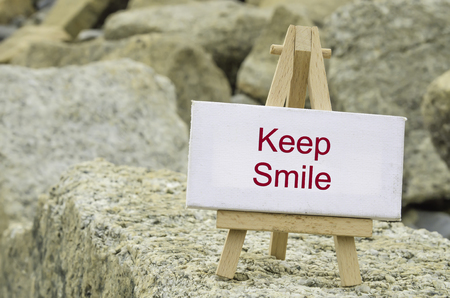 conceptual image,  word KEEP SMILE on white canvas frame and wooden tripod stand.blur rock textures background