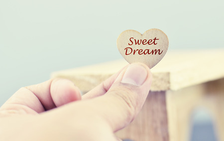focus on background: conceptual image,romantic look hand holding heart made from wood with word SWEET DREAM over blurred and selective focus background Stock Photo