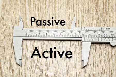 Business motivation and finance concept, vernier caliper with word PASSIVE vs ACTIVE over wooden floor and alphabetical word made from wood background
