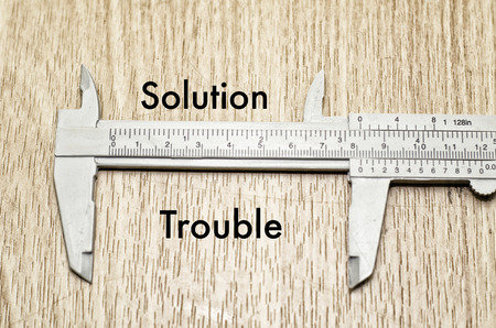vernier caliper: Business motivation and finance concept, vernier caliper with word SOLUTION vs TROUBLE over wooden floor and alphabetical word made from wood background