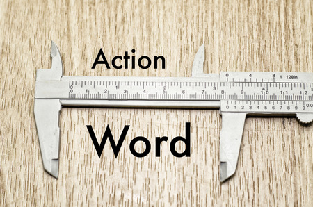 vernier caliper: Business motivation and finance concept, vernier caliper with word ACTION vs WORD over wooden floor and alphabetical word made from wood background Stock Photo