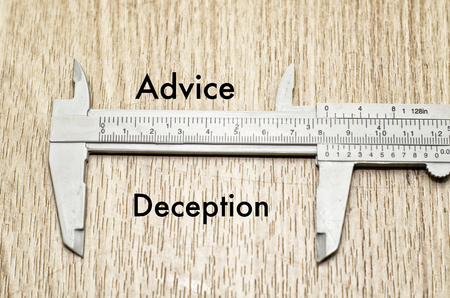 Business motivation and finance concept, vernier caliper with word ADVICE vs DECEPTION over wooden floor and alphabetical word made from wood background