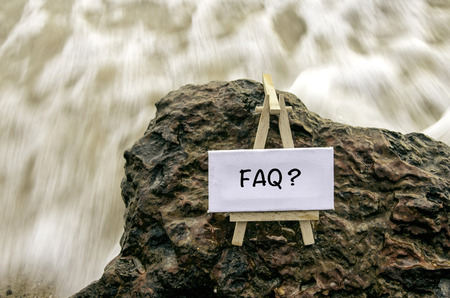 Image concept word FAQ on white canvas frame with wooden tripod.background motion blur white wave flow hitting wet and mossy rock on the beach.