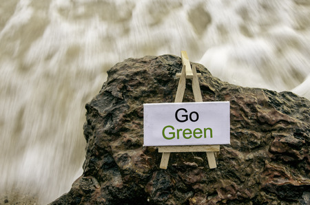 Image concept, word GO GREEN on white canvas frame with wooden tripod.background motion blur white wave flow hitting wet and mossy rock on the beach.