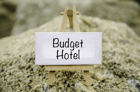 conceptual image,  word BUDGET HOTEL on white canvas frame and wooden tripod stand. blur rock textures background