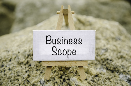 conceptual image,  word BUSINESS SCOPE white canvas frame and wooden tripod stand. blur rock textures background