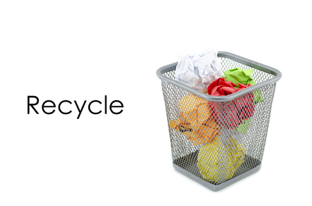 to thrash: conceptual image with word RECYCLE over crumple paper in metal dustbin and isolated white background Stock Photo